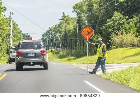 Street Worker Shows Slow Sign