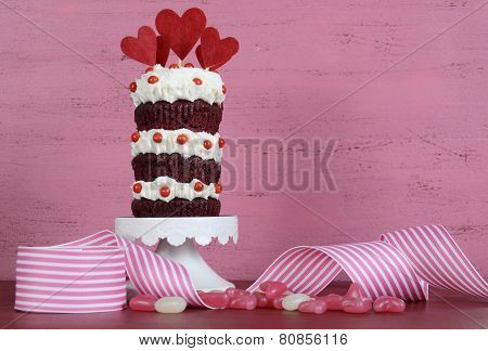 Novelty Triple Layer Red Velvet Cupcake On White Cake Stand With Ribbons And Candy Against A Vintage