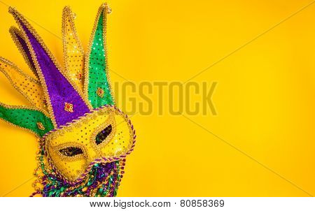 Assorted colorful Mardi Gras mask on yellow background with beads