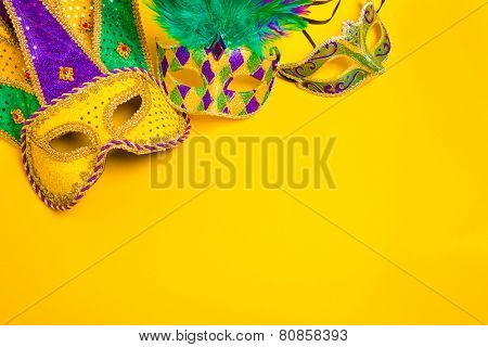 Assorted colorful Mardi Gras mask on yellow background poster