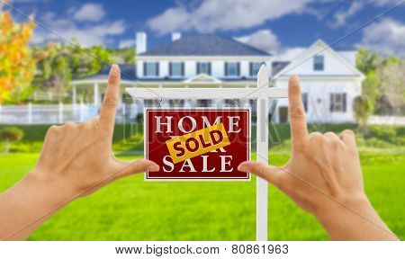 Female Hands Framing Sold Home For Sale Real Estate Sign in Front of New House.