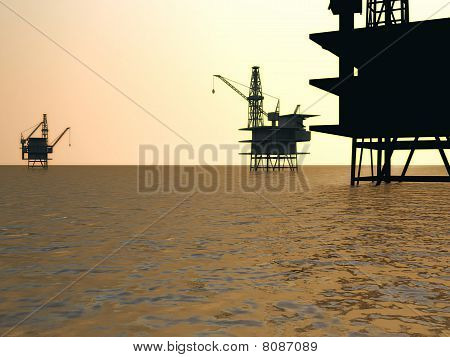 Oil rigs silhouetted in sea