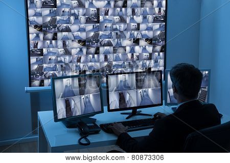 Man In Control Room Monitoring Cctv Footage