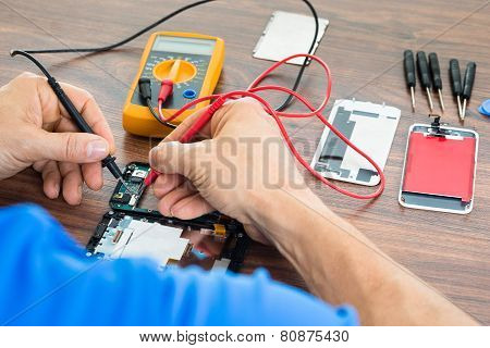 Technician Repairing Cellphone With Multimeter
