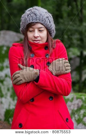 Young woman shivering with cold and embracing herself on a forest wearing a red overcoat, a beanie and gloves during winter  poster