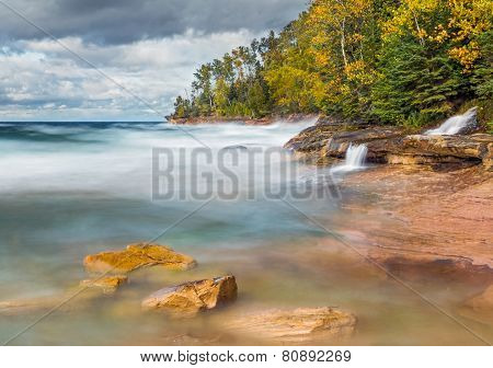 Photographed with a long exposure waves crash on the rocky coast of Miner's Beach at Upper Peninsula Michigan's Pictured Rocks National Lakeshore as Elliot Falls spills into Lake Superior. poster