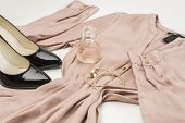 Elegant ladies fashion ensemble with a stylish dress classic patent leather black court shoes gold bangles and bottle of perfume or scent laid out ready to wear on a white background low angle poster