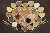 Grain food selection on a heart shaped wooden board and in porcelain bowls with wheat ears over lokta paper background. poster