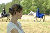 girl watching a horsewoman ride in blur poster