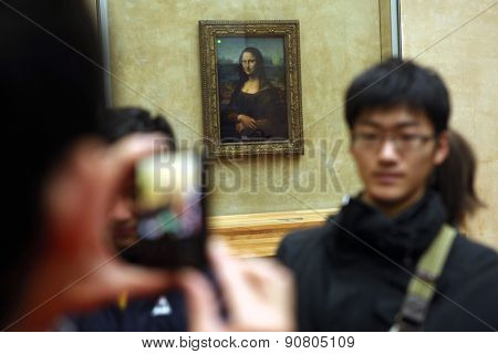 PARIS, FRANCE - JANUARY 7, 2013: Visitors take pictures in front of Mona Lisa by Leonardo da Vinci in the Louvre Museum in Paris, France.