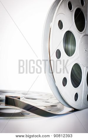 Vintage 35 mm movie cinema reel on white background film unrolled and copy space vertical frame poster