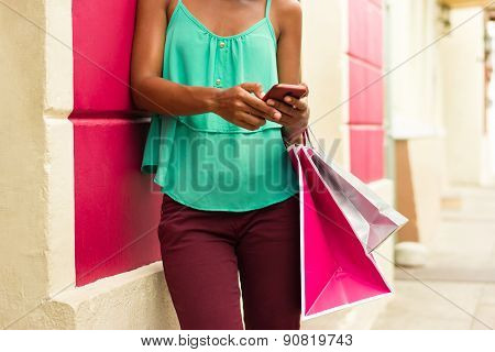 African American Girl Sending Text Messaging On Phone Shopping Bags