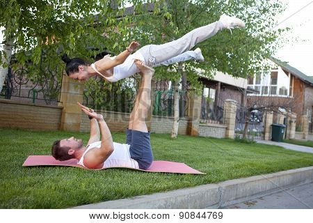 An attractive man and woman practice tantra yoga on a grass before the house