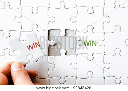 Hand with missing jigsaw puzzle piece completing the wordS WIN WIN. Business concept image for completing the final puzzle piece. poster