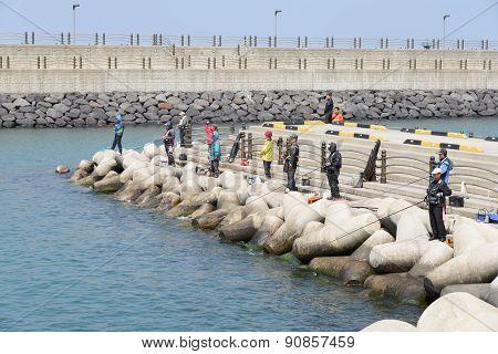 Jeju-do, Korea - April 08, 2015: Fishermen On A Breakwater