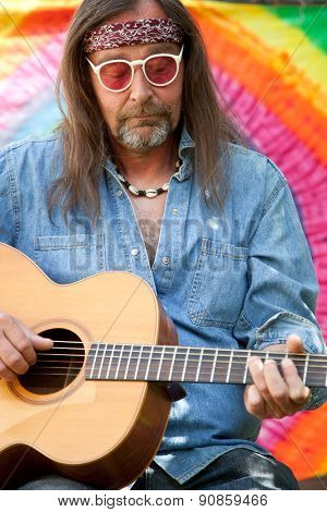 Bearded Middle-aged Hippie Man Playing The Guitar