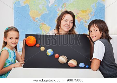 Kids with their science teacher showing their home project - planets of the solar system