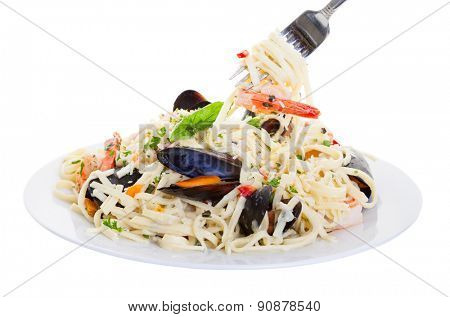 Plate of pasta with shrimp, mussels and mixed seafood. Shot on a white background.