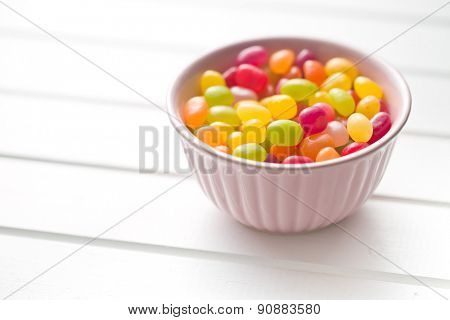 jelly beans in bowl on white table poster