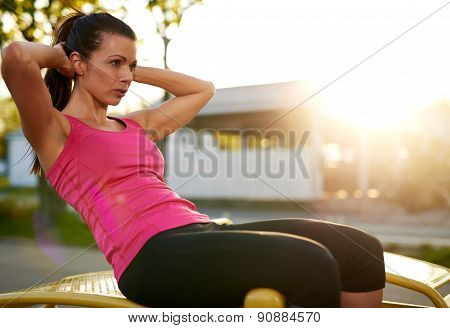 Side View Of Woman Doing Situps Outside.