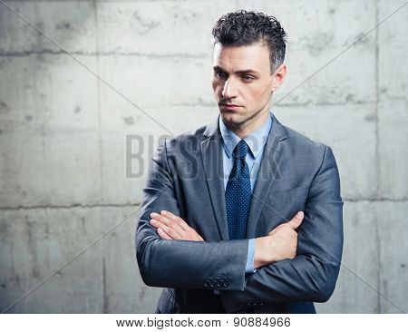 Portrait of a pensive businessman standing with arms folded over concrete wall and looking away
