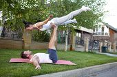 An attractive man and woman practice tantra yoga on a grass before the house poster