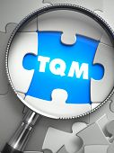 TQM - Total Quality Management - Word on the Place of Missing Puzzle Piece through Magnifier. Selective Focus. poster