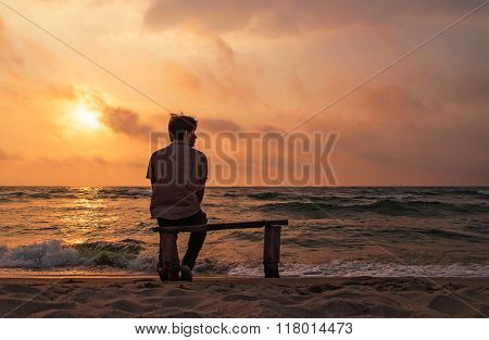 Lonely man sits on a bench on the coast enjoying sunset