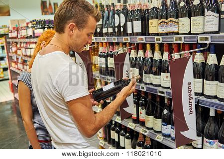 BEGLES, FRANCE - AUGUST 13, 2015: customers choose wine at Simply Market. Simply Market is a brand of French supermarkets. This brand is a new concept to eventually replace Atac supermarkets