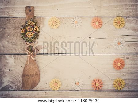 Wooden background with kitchen utencil and flowers