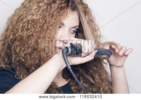 Woman With A Hair Straightener.