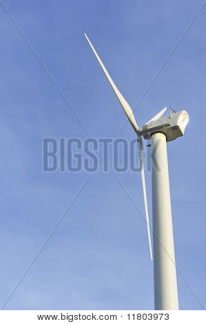 Side View Of Eco-friendly White Wind Turbine Against A Clear Blue Sky