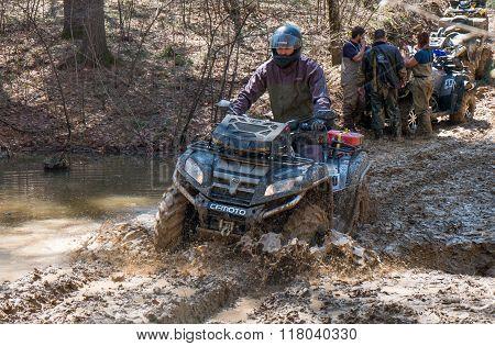 ATV rides through the mud with a big splash