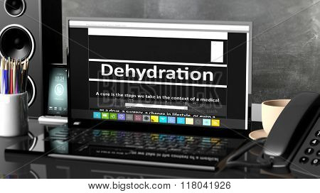 Laptop with Dehydration  information on screen, on desktop with office objects.
