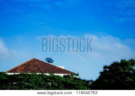 Satellite dish on roof with blue sky