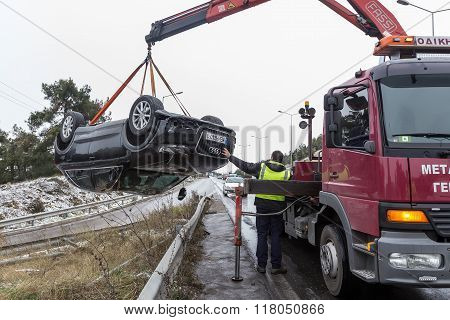 Man Towing Damaged Car Over A Tow Truck On The Side Of The Road In Thessaloniki, Greece.