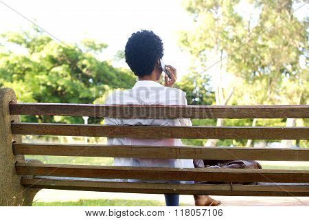 African Woman Sitting On A Park Bench Using Cell Phone