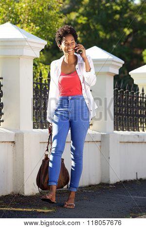 Woman Walking Outdoors Using Mobile Phone