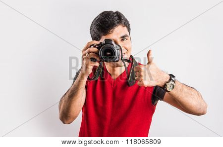 Close-up of young handsome indian photographer taking a photograph, asian man holding camera, indian