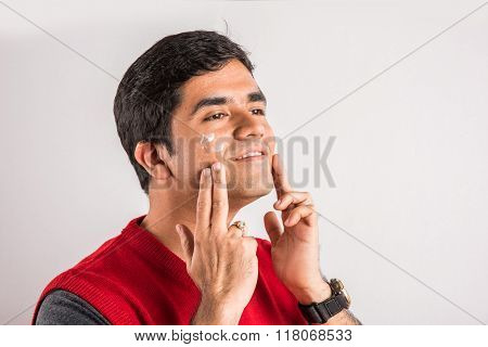 Handsome indian man applying sunscreen on his face, asian man applying face cream, Young indian man