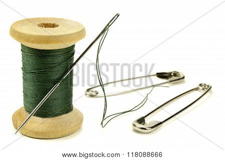 Wooden Coil With Threads, Needle And Safety Pin For Sewing On A White Background