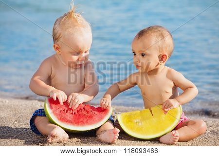 On beach asian baby girl and white boy eat fruits