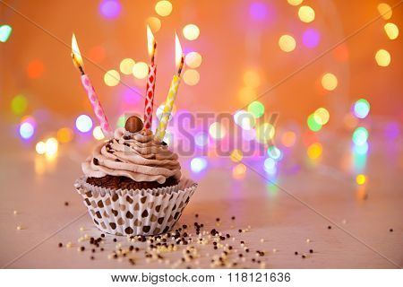 Tasty chocolate cupcake with butter cream and candles on a glitter background