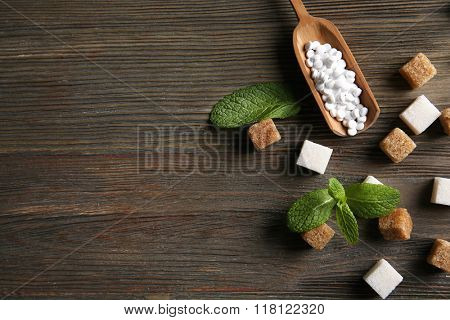 Sugar cubes and stevia  on wooden background