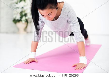 Young latin woman warming up and doing push ups at home fitness healthy lifestyle diet concept.