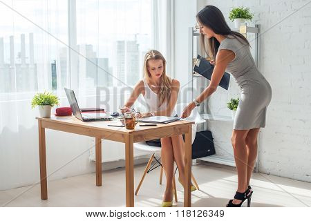 Two young woman working together in office. Subordinate and boss.