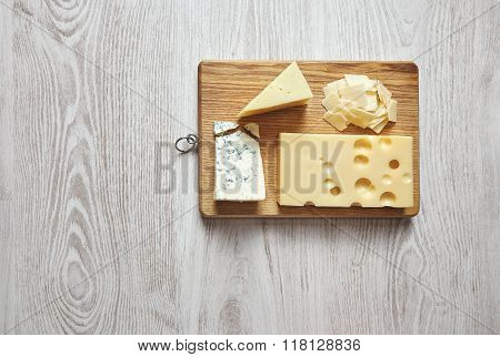 Set Of Four Cheeses Isolated On White Table Board