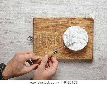 Man Hands Cut Piece Of Camembert On Wooden Table