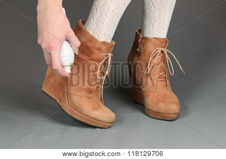 Female Legs In Brown Suede Boots On A Gray Background. Woman Cleaning Her Suede Shoes