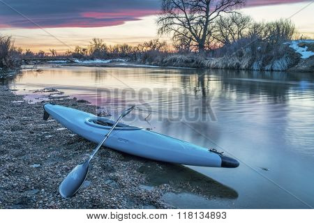 whitewater kayak at dusk on St Vrain Creek near Platteville, Colorado, winter scenery, end of paddling trip concept